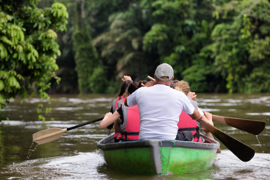 People exploring a wild nature area by rowing boat in Tortuguero National Park, Costa Rica.